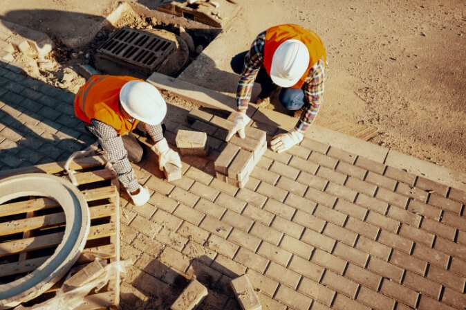 Construction workers at Mapa Group lay bricks